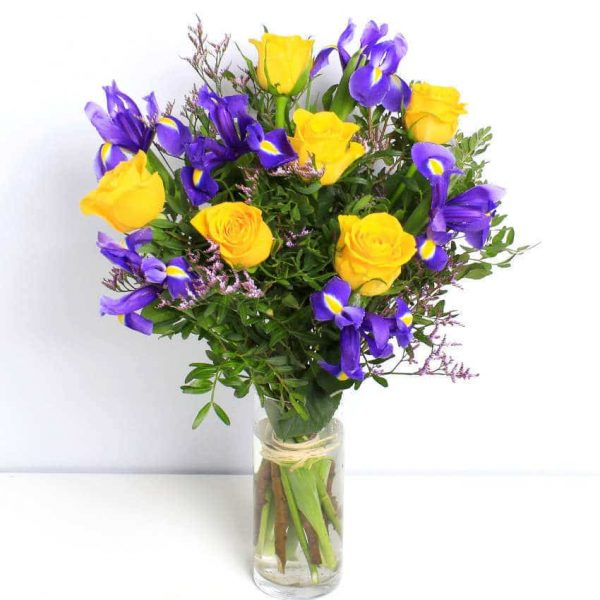 yellow roses and purple iris flowers in a vase