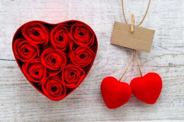 Red roses in a heart-shaped box and red Cherry Hearts